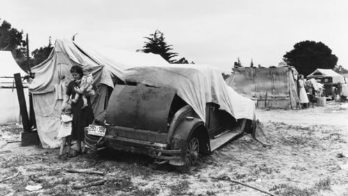 Photo of a car used as a tent to demonstrate depth of Great Depression in these economic predictions.