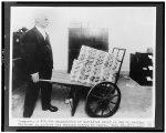 Treasury employee moves wheelbarrow full of money, destined for destruction. (National Photo Company Collection, Public domain, via Wikimedia Commons)